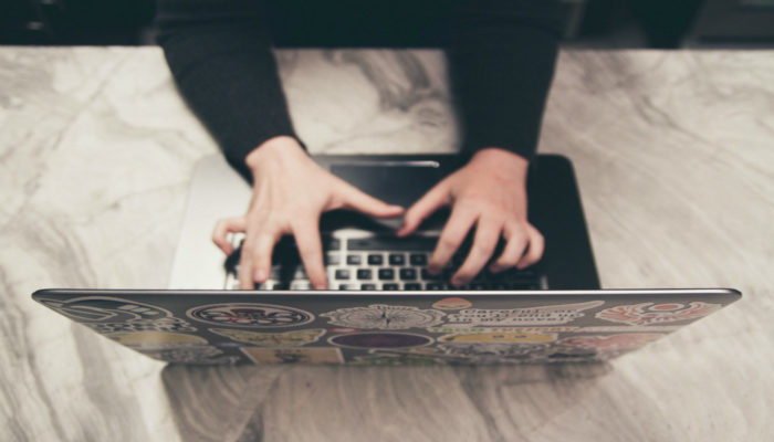 Mãos digitando em notebook representam como aumentar as vendas
