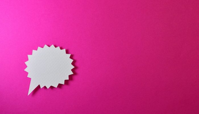 Balão de diálogo sobre fundo rosa representando o chat online