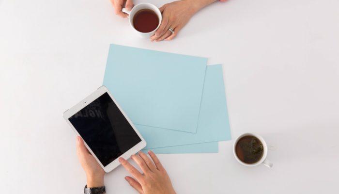 Mesa com papéis, mãos segurando um tablet e outra, segurando uma xícara de café, representando o planejamento dos canais de venda