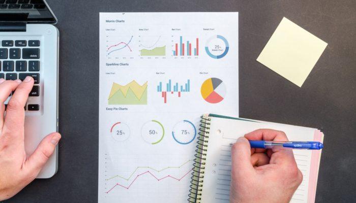 Pessoa escrevendo em folha de gráficos representa os dados de clientes