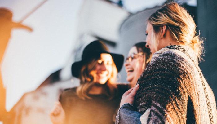 Três mulheres conversam felizes