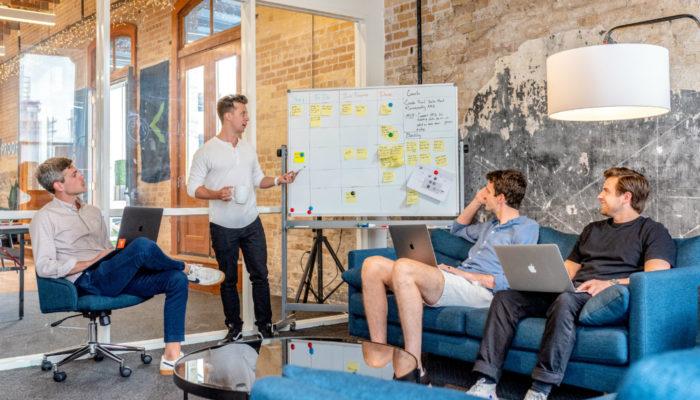 Profissionais jovens em reunião de planejamento representam as vantagens do ERP
