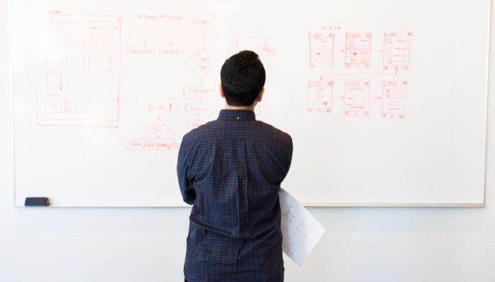 Homem analisa lousa, como quem faz o planejamento do ecommerce