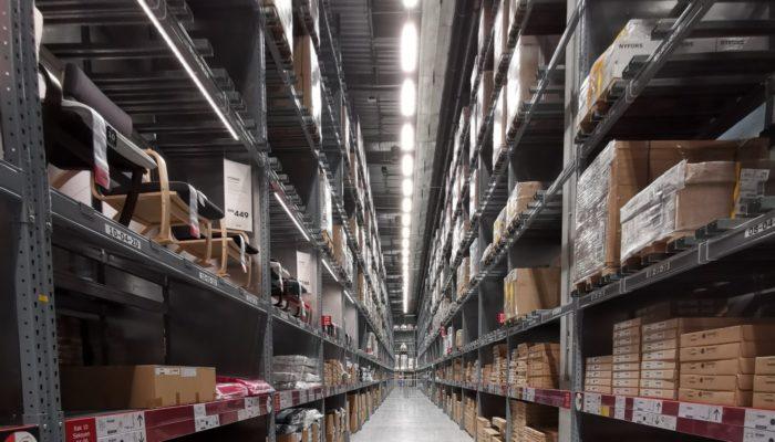 Imagem de prateleiras com produtos em um grande armazém, representando a gestão de estoque