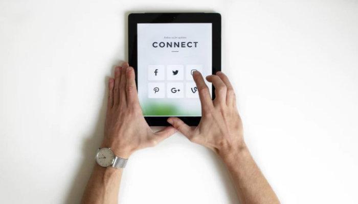 Homem mexendo em tablet representa como escolher as redes sociais para empresa