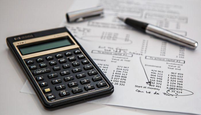 Calculadora ao lado de caneta e papel com anotações numéricas representam o papel do contador