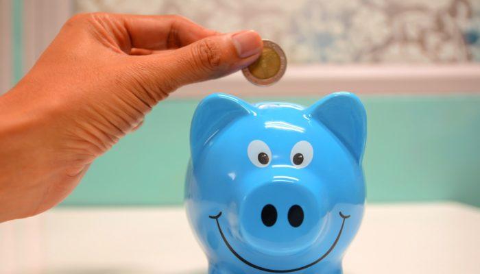 Cofre de porquinho azul com mão depositando uma moeda, representando a gestão financeira