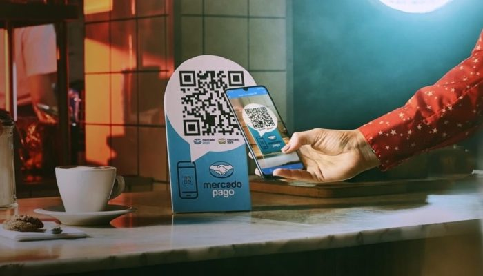 Celular apontando para um QR code em uma plaquinha azul, representando como cobrar pelo Mercado Pago