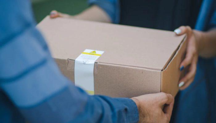 Mãos entregam caixa de papelão, representando como funciona o frete para ecommerce