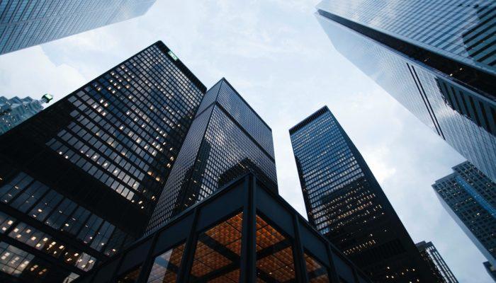 Vista de baixo de prédios comerciais, representando banco para abrir uma conta mei