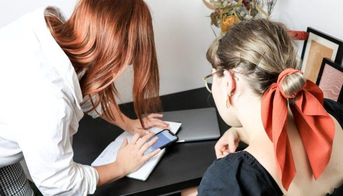 Mulheres mexem em smartphone, conferindo se sofreram shadowban no Instagram