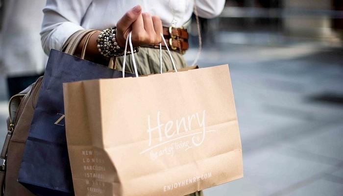 Mão de uma mulher carregando sacolas de compra para representar como aumentar as vendas.