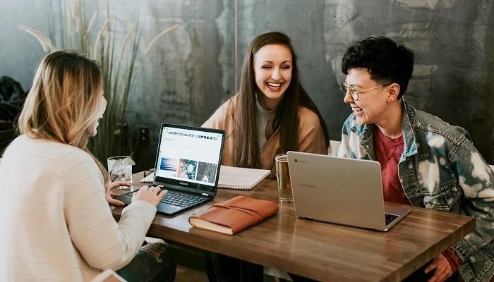 tres mulheres conversando em uma mesa
