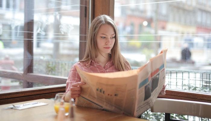 Mulher lendo jornal sentada em café
