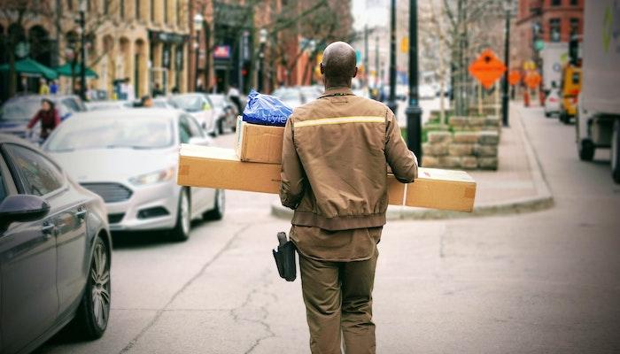Entregador andando na rua com caixas de encomendas
