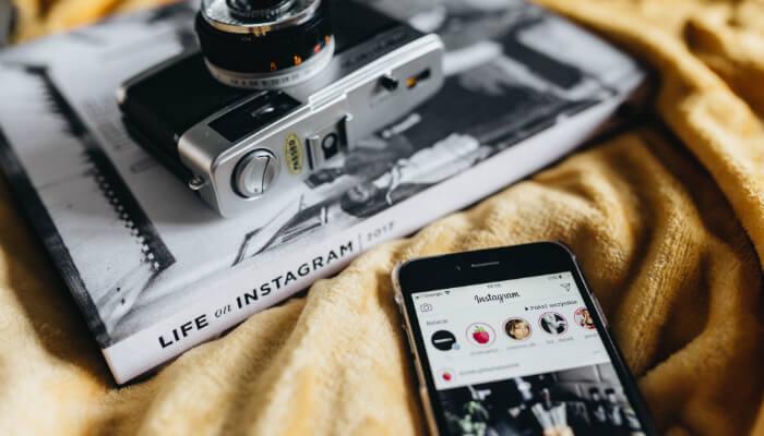 Celular com o aplicativo aberto, próximo a uma revista e a uma câmera analógica, representa a automação para Instagram