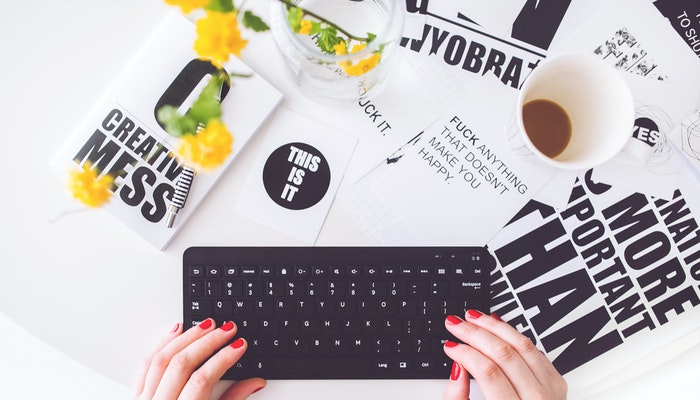 Mãos digitando em um teclado, exemplo de como produzir conteúdo
