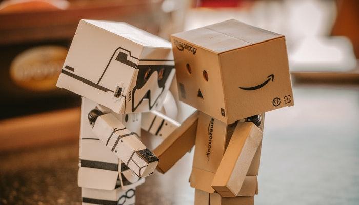 Dois pequenos robôs de papelão, representando a pergunta