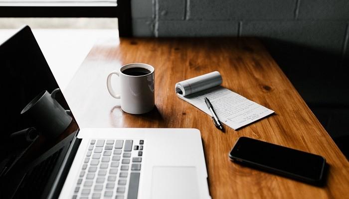 Mesa de trabalho com notebook e bloco de notas representa como vender produtos digitais