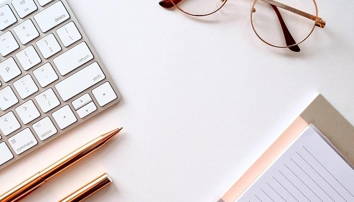 Teclado de computador, caneta, bloco de notas e óculos, o material para fazer uma introducao