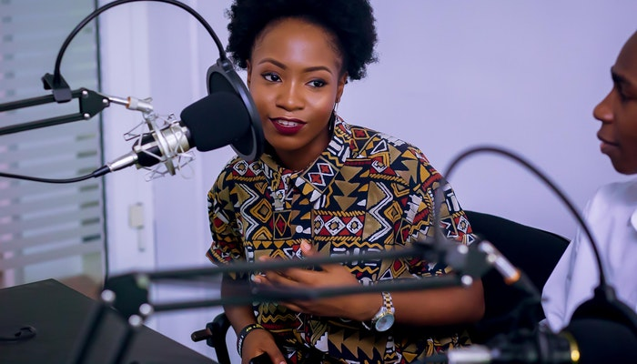 Mulher sentada, falando próxima a um microfone de estúdio, representando como fazer um podcast
