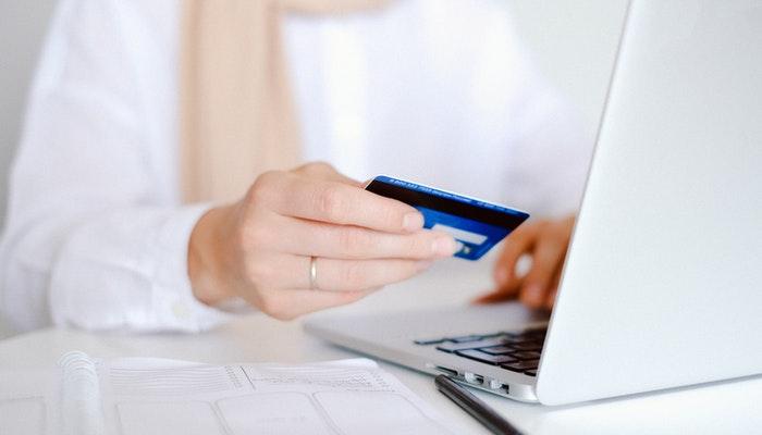 Imagem de uma mulher segurando um cartão de crédito em frente a um computador. Representando uma compra online.