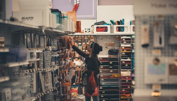 Mulher mexendo na prateleira de uma loja, representando o que é PDV e como o sistema ajuda na gestão