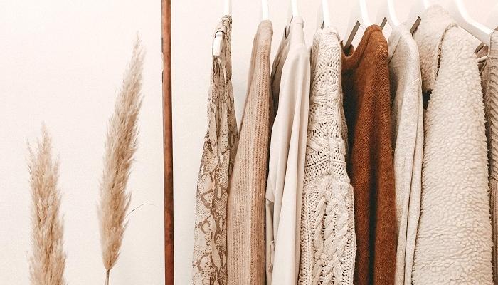 Imagem de roupas penduras em cabides para representar como tirar fotos de roupas para vender.