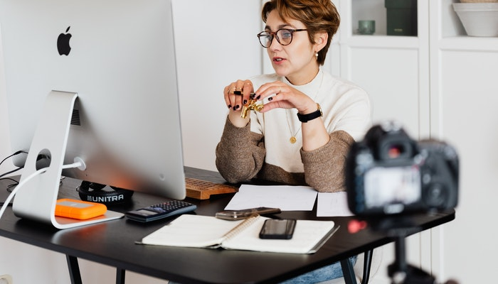 Imagem de uma mulher em seu escritório gravando vídeos para sua empresa, representando a venda de serviços na internet.