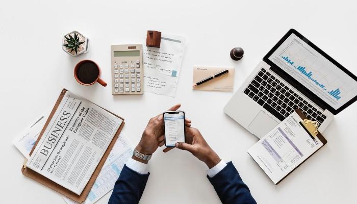 Mãos mexendo em celular, sobre mesa com jornal, notebook, caneta, calculadora e itens que remetem à organização para montar um ecommerce do zero
