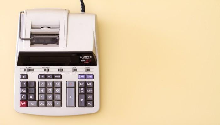 Máquina de calcular com bobina, representando o cálculo da estrutura de custos