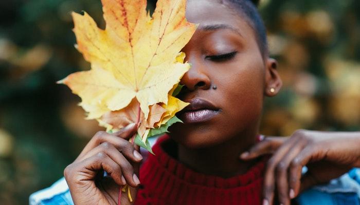 Mulher com os olhos fechados e uma folha encostada no rosto, representando como desenvolver a inteligência emocional no trabalho
