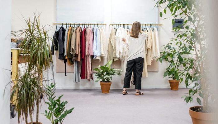 Mulher mexendo em arara de roupas em uma loja, representando a pop-up store