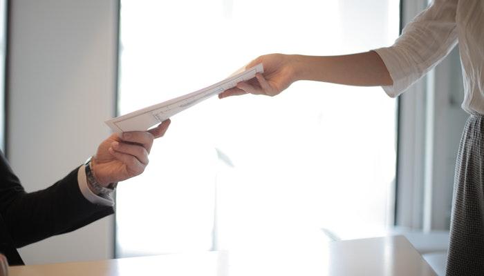 Pessoa passando documento a outra, representando como definir o CNAE para ecommerce