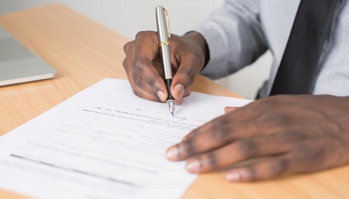Mão assinando um documento, representando como registrar uma marca