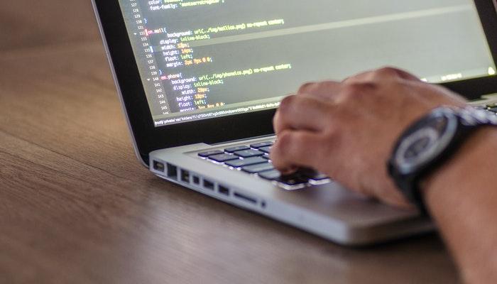 Tela de computador com códigos de HTML e mãos digitando