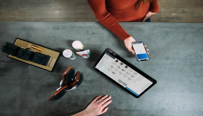 Visão de cima de um balcão de loja, com uma tela de computador mostrando um e-commerce e uma pessoa segurando um celular, representando as vendas online.