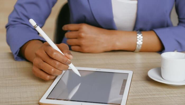Mulher escreve em tablet, como quem faz a descrição de produtos