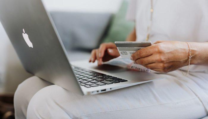 Persona comprando en e-commerce con tarjeta de crédito en la mano y computadora portátil
