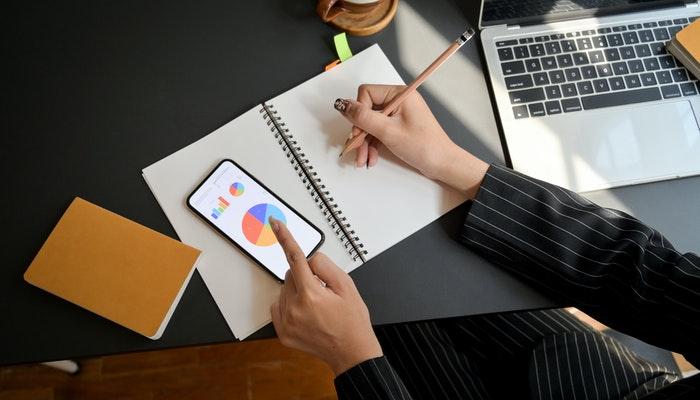 Imagem mostrando um gráfico e uma pessoa fazendo anotações no caderno, representando a análise de dados para melhorias na experiência do cliente