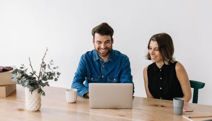 hombre y mujer sonrientes trabajando con laptop