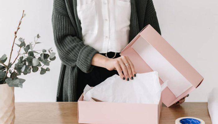 Mujer empacando un producto en una caja rosa
