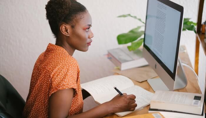 Mulher escreve enquanto olha para tela do computador, como se estudasse com o Google para PMEs