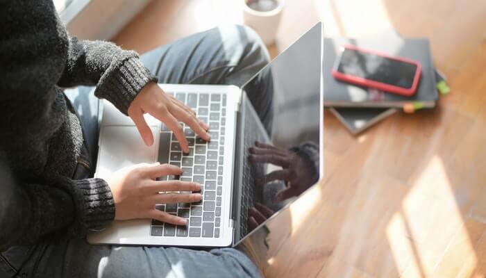 Mulher digita em computador, com celular ao lado, representando o trabalho com marketing digital