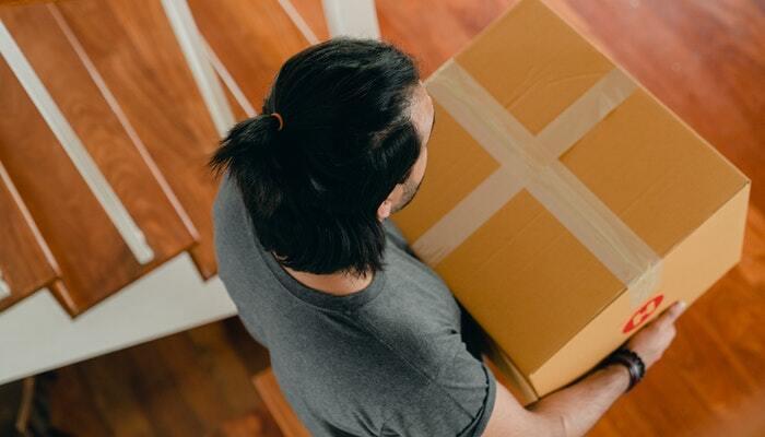 Homem segurando caixa de encomenda