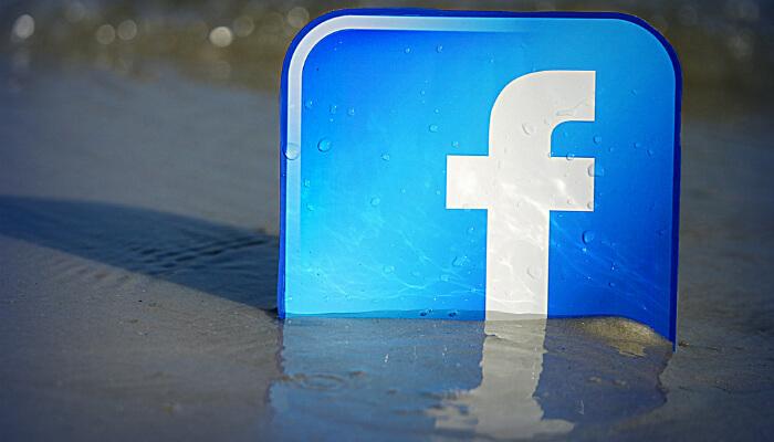 Imagem do logo do Facebook sobre uma areia molhada na praia