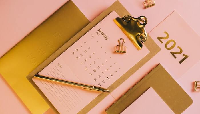 Foto de mesa de escritório com prancheta, caneta e folhinha, representando o calendário comercial de 2021