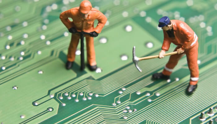 Foto de bonecos de operários de construção sobre placa de vídeo, representando como pagar pelos anúncios no Google Ads