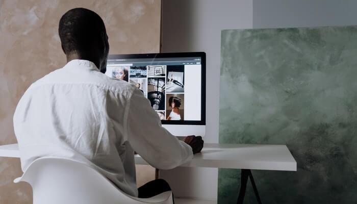 Homem visto de costas mexendo no computador, representando como registrar um domínio