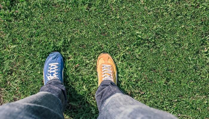 Pernas com um pé de tênis azul, outro, laranja sobre gramado, representando o comparador de preço